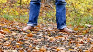 Schamane gerhard Zirkel steht barfuss im Wald